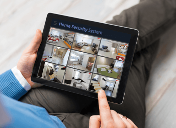 Man sitting on couch holds tablet with home security system pulled up
